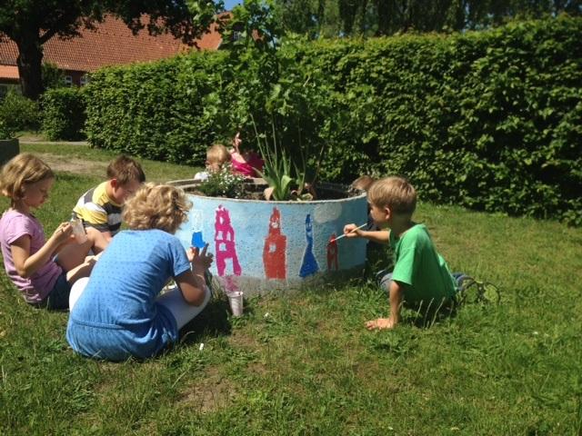 """Wir Kinder der AG """"Schulhofverschönerung"""" haben mit Frau Buss die grauen Blumenkübel bemalt."""